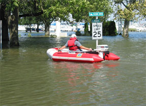 Rescue personel in life jacket on flotation raft on flooded street